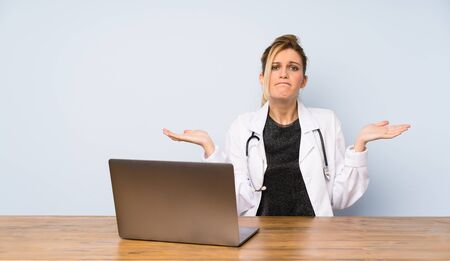 Blonde doctor woman having doubts while raising hands
