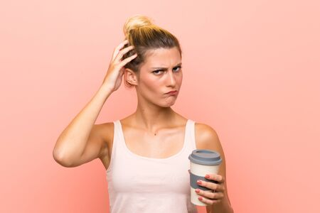 Young blonde woman holding a take away coffee having doubts and with confuse face expression Stock fotó