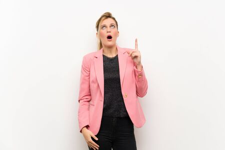 Young blonde woman with pink suit pointing up and surprised Stock fotó