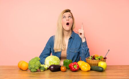 Young blonde woman with many vegetables pointing up and surprised