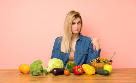 Young blonde woman with many vegetables unhappy and pointing to the side Stock fotó