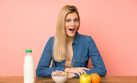 Young blonde woman with bowl of cereals with surprise facial expression