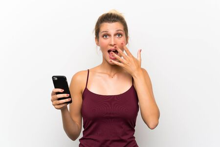 Young blonde woman using mobile phone with surprise facial expression
