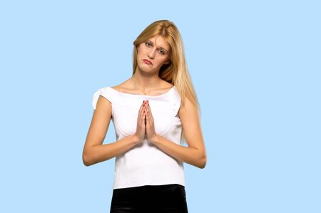 Young blonde woman keeps palm together. Person asks for something on isolated blue background