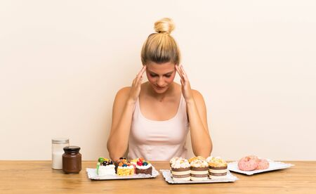 Young woman with lots of different mini cakes in a table unhappy and frustrated with something. Negative facial expression