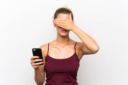 Young blonde woman using mobile phone covering eyes by hands