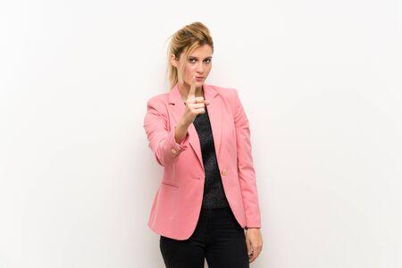 Joven rubia con traje rosa frustrada y apuntando hacia el frente