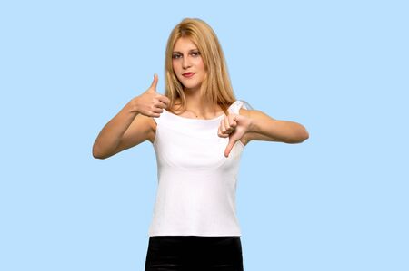 Young blonde woman making good-bad sign. Undecided between yes or not on isolated blue background 写真素材