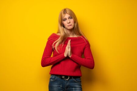 Blonde woman over yellow wall keeps palm together. Person asks for something Stock Photo - 130143003