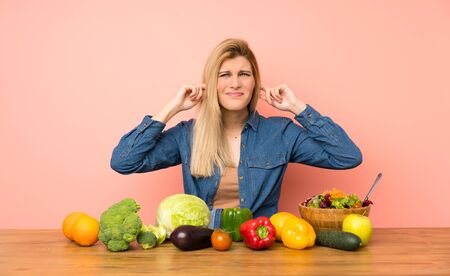 Young blonde woman with many vegetables frustrated and covering ears