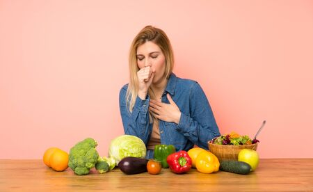 Young blonde woman with many vegetables is suffering with cough and feeling bad