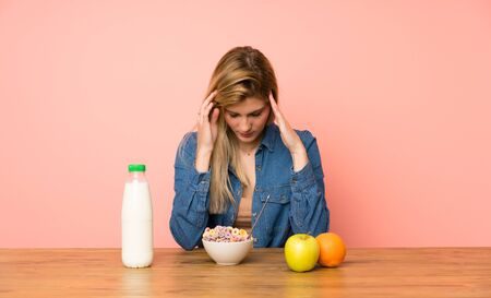 Young blonde woman with bowl of cereals unhappy and frustrated with something. Negative facial expression