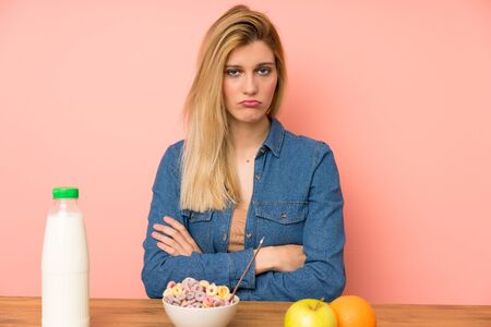 Young blonde woman with bowl of cereals sad