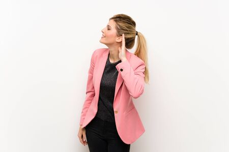 Young blonde woman with pink suit listening to something by putting hand on the ear