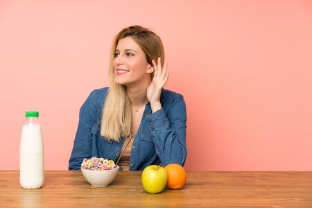 Young blonde woman with bowl of cereals listening something Zdjęcie Seryjne
