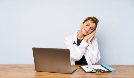 Blonde doctor woman making sleep gesture in dorable expression 版權商用圖片