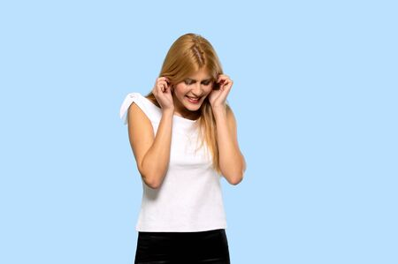 Young blonde woman covering ears with hands. Frustrated expression on isolated blue background