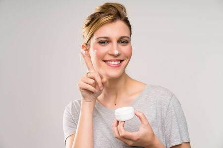 Young blonde woman with makeup brush with moisturizer