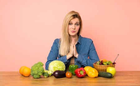 Young blonde woman with many vegetables keeps palm together. Person asks for something