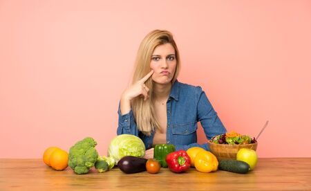 Young blonde woman with many vegetables Looking front