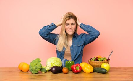 Young blonde woman with many vegetables frustrated and takes hands on head