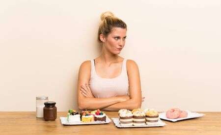Young woman with lots of different mini cakes in a table thinking an idea
