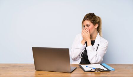 Blonde doctor woman covering mouth and looking to the side
