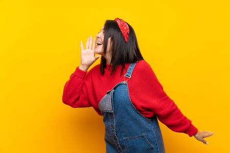 Young Mexican woman with overalls over yellow wall shouting with mouth wide open to the lateral