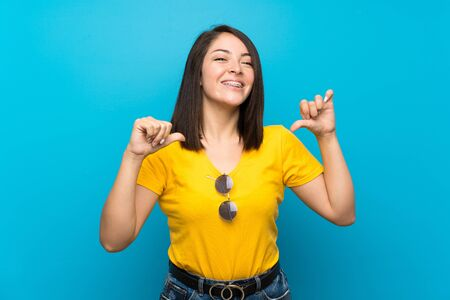 Young Mexican woman over isolated blue background proud and self-satisfied