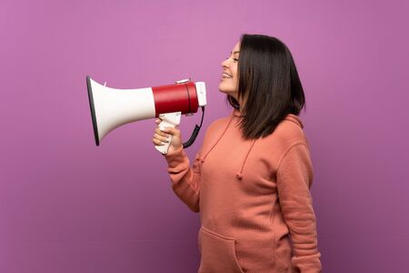 Young Mexican woman over isolated background shouting through a megaphone
