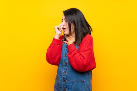Young Mexican woman with overalls over yellow wall is suffering with cough and feeling bad Stock fotó