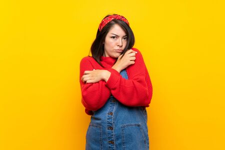 Young Mexican woman with overalls over yellow wall freezing Banque d'images - 130155858