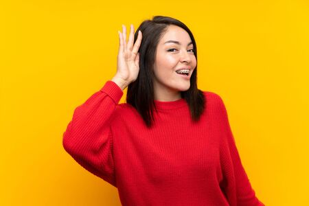 Young Mexican woman with red sweater over yellow wall listening something