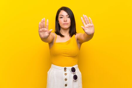 Young Mexican woman over isolated yellow background making stop gesture and disappointed