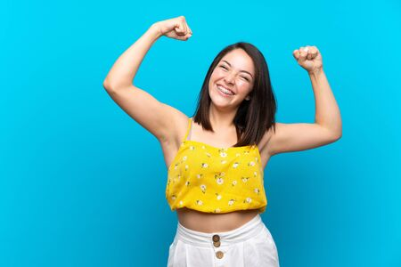 Young Mexican woman over isolated blue background celebrating a victory