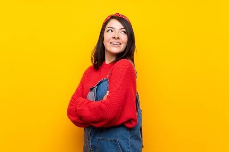 Young Mexican woman with overalls over yellow wall with arms crossed and happy
