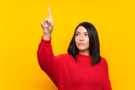 Young Mexican woman with red sweater over yellow wall touching on transparent screen