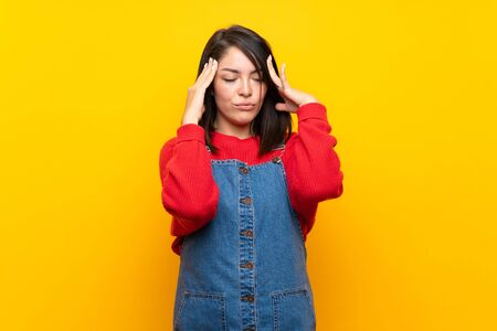 Young Mexican woman with overalls over yellow wall with headache Standard-Bild