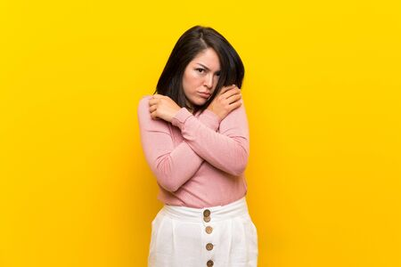 Young Mexican woman over isolated yellow background freezing Banque d'images - 130156086