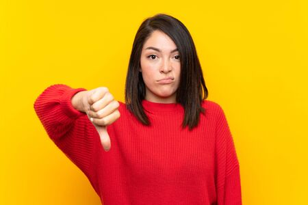 Young Mexican woman with red sweater over yellow wall showing thumb down sign