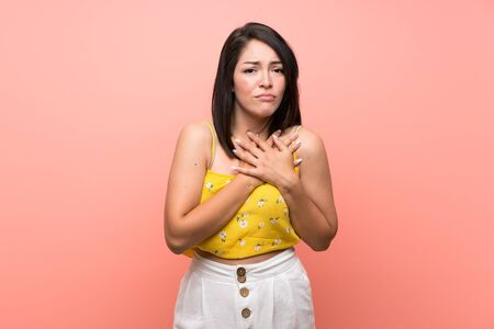Young Mexican woman over isolated wall having a pain in the heart