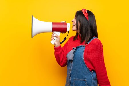 Young Mexican woman with overalls over yellow wall shouting through a megaphone