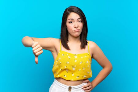 Young Mexican woman over isolated blue background showing thumb down sign