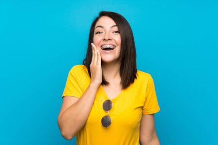 Young Mexican woman over isolated blue background with surprise and shocked facial expression