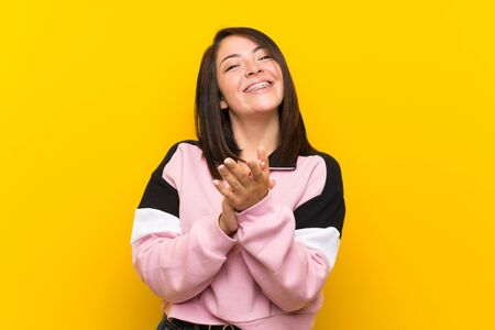 Young Mexican woman over isolated yellow background applauding