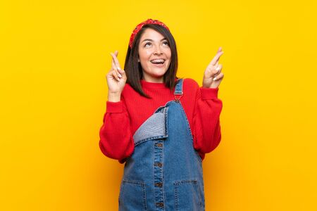 Young Mexican woman with overalls over yellow wall with fingers crossing and wishing the best Standard-Bild