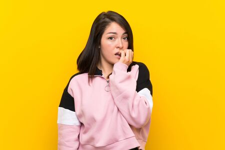 Young Mexican woman over isolated yellow background nervous and scared