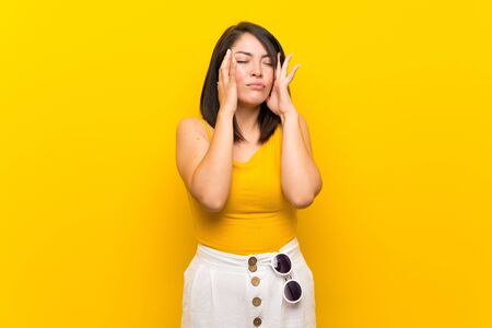 Young Mexican woman over isolated yellow background with headache