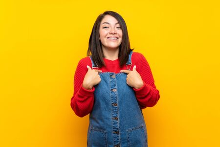 Young Mexican woman with overalls over yellow wall with surprise facial expression Stock fotó