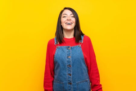 Young Mexican woman with overalls over yellow wall with surprise facial expression Stock fotó - 130156562